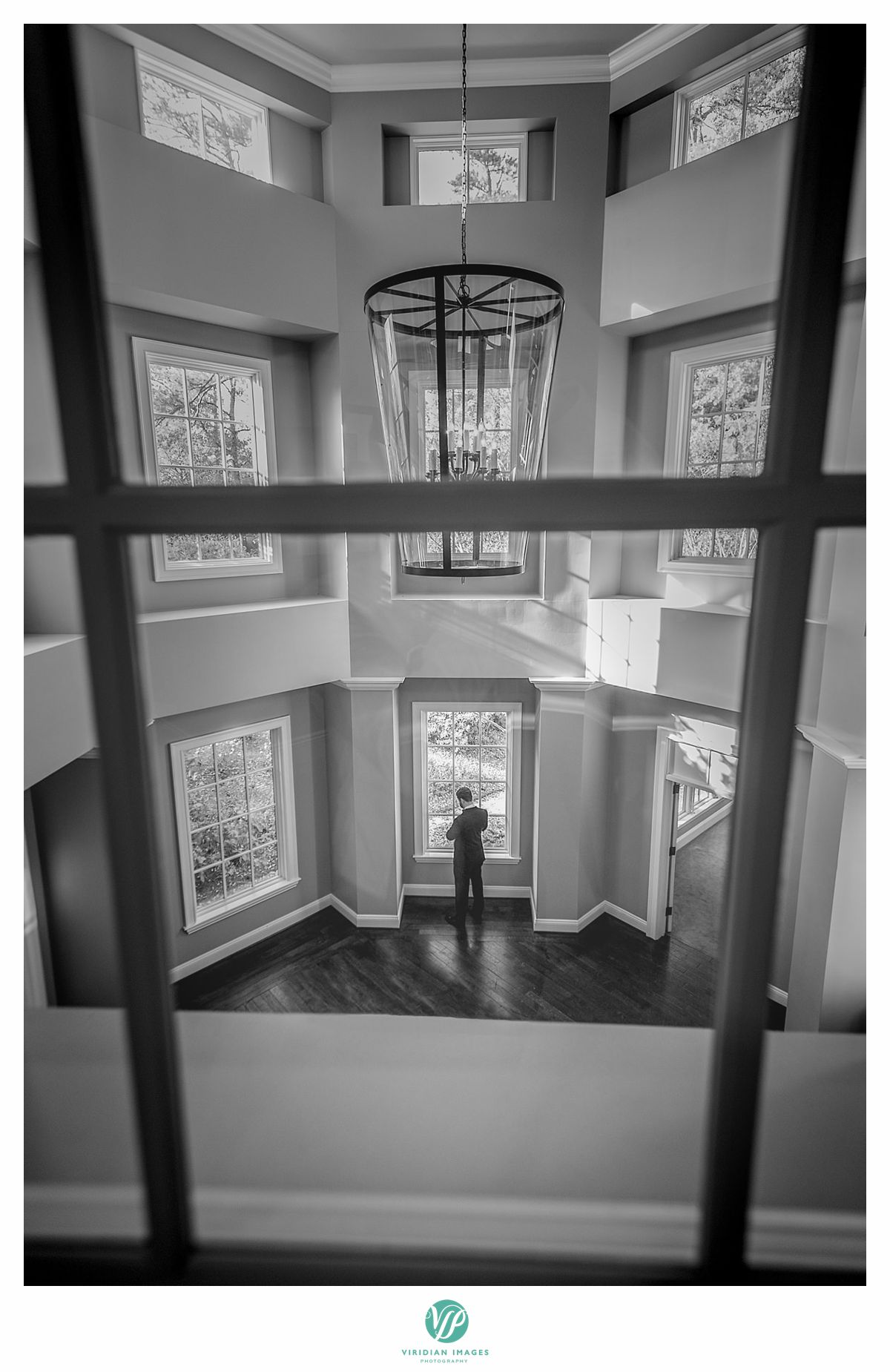 Creative groom portrait through window pane