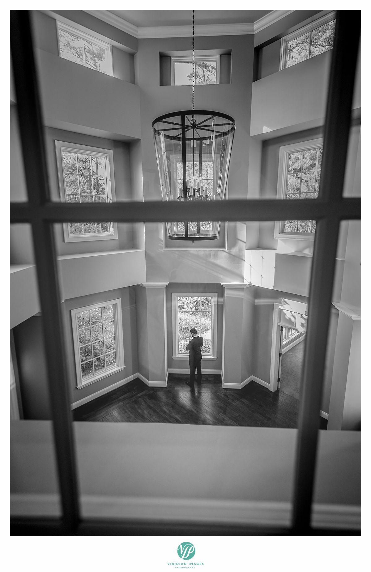 Creative groom portrait through window pane