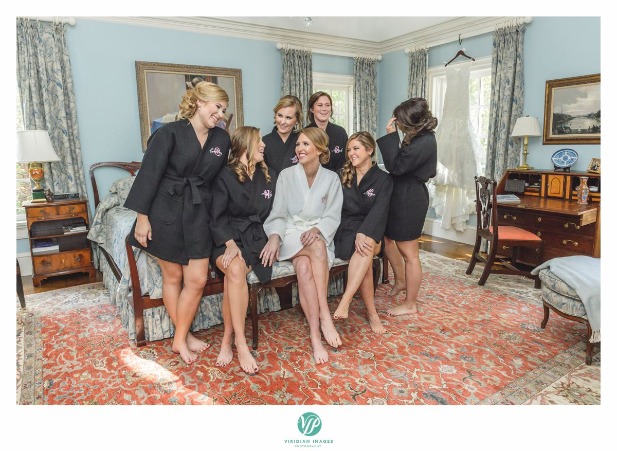Bridesmaids in monogrammed black robes with bride