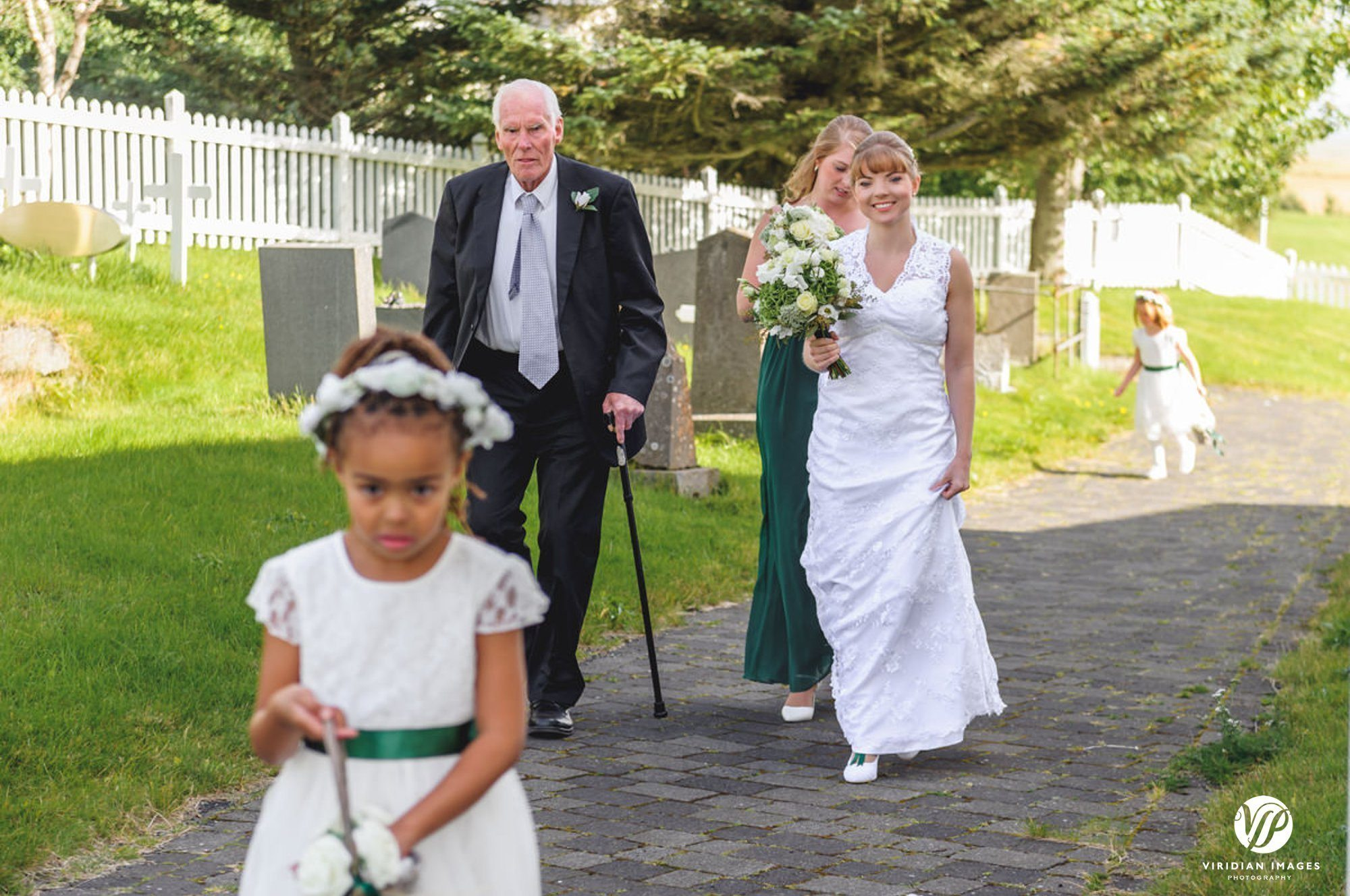 Bride walking with father and flower girl in Oddakirkja church Iceland