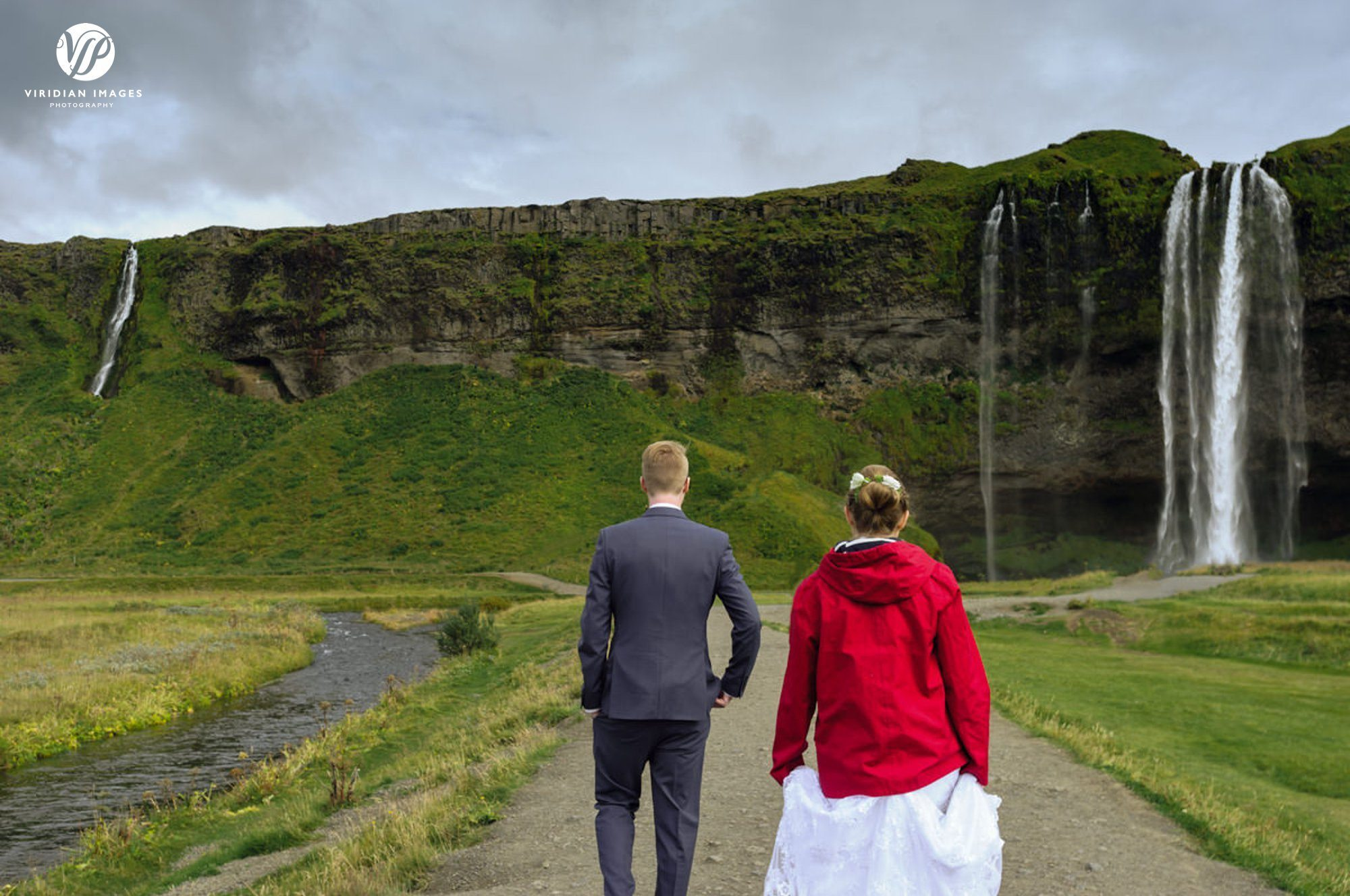 Bride and groom walking to Seljalandsfoss