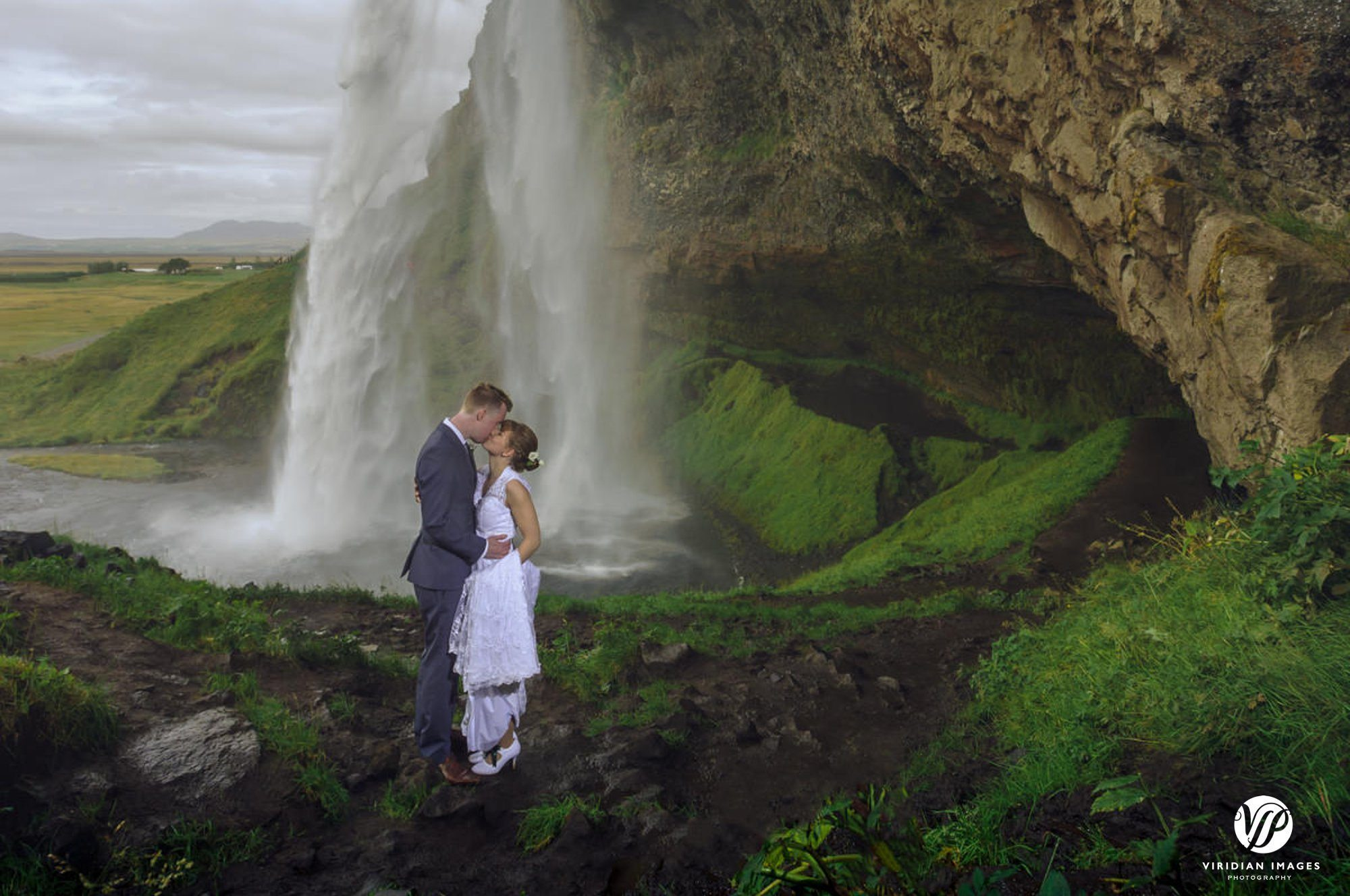 Kissing under Seljalandsfoss waterfall in Iceland