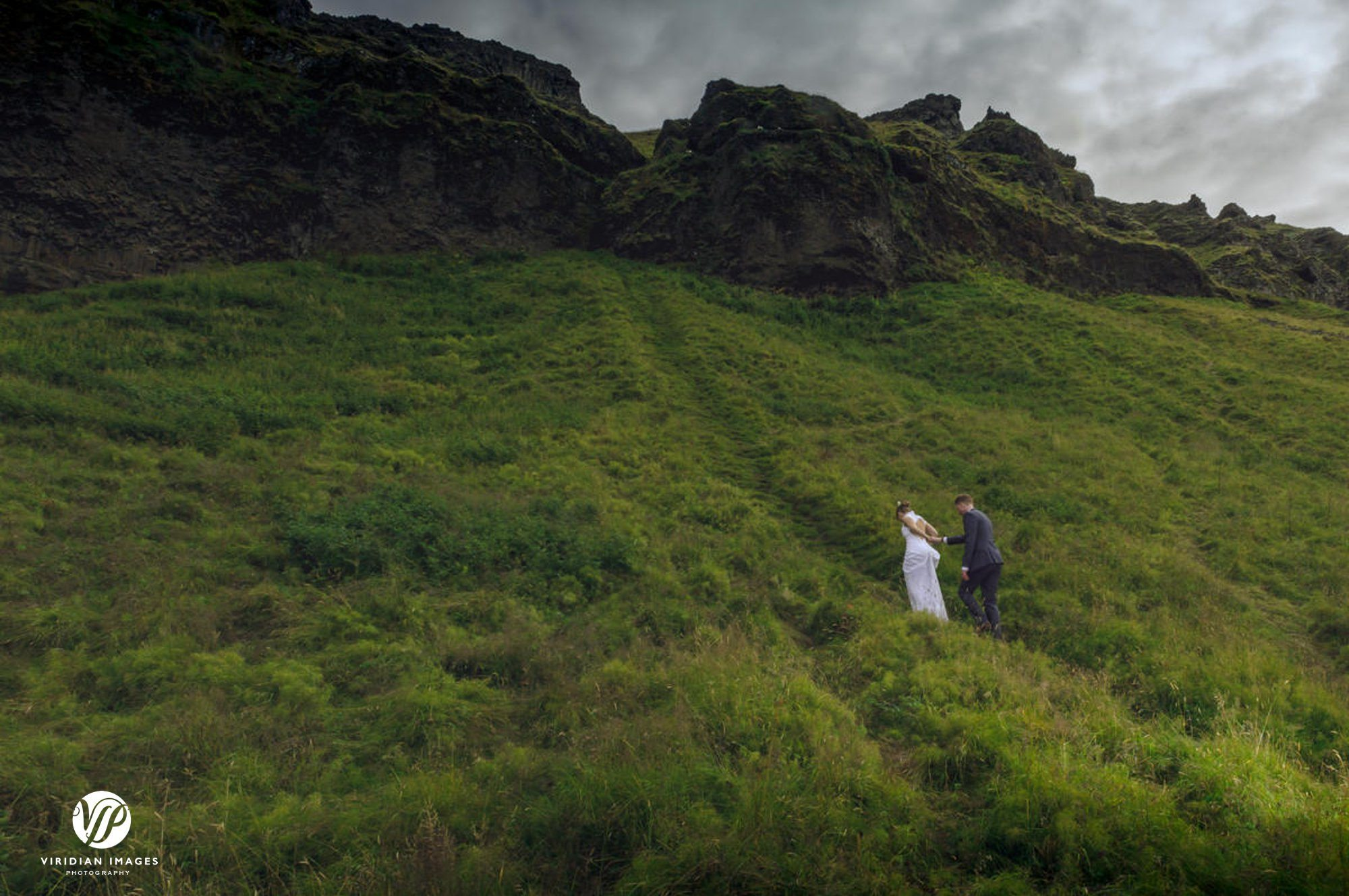 Bride and groom climbing side of mountain by Seljalandsfoss waterfall Iceland