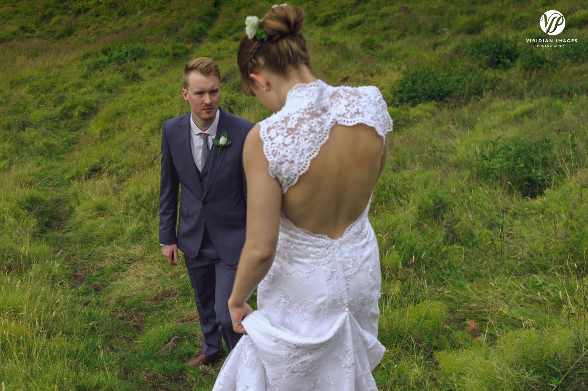 Groom looks emotionally as he helps his new bride down the mountain in Iceland