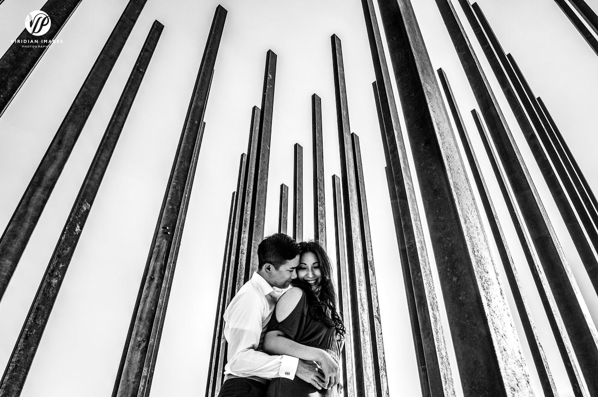 couple hug from below metal posts