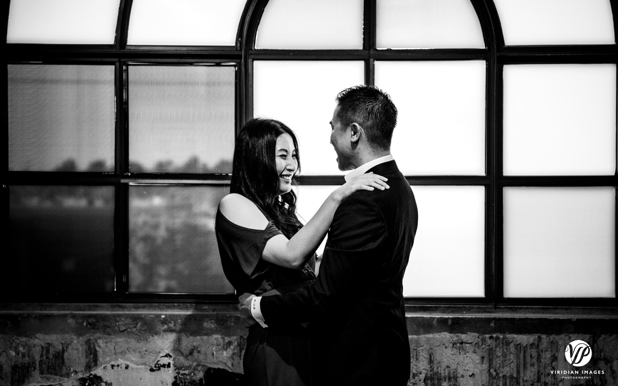 couple face each other laughing black and white