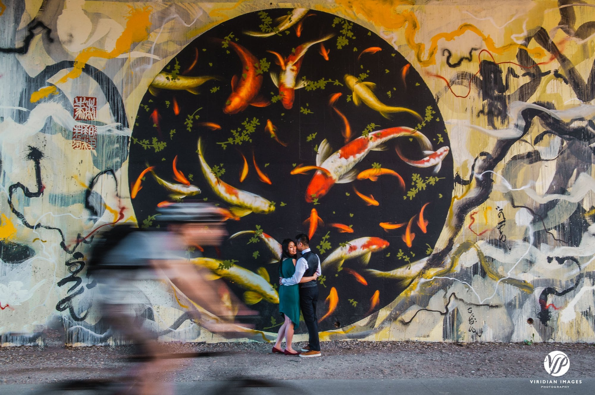 couple facing fish mural beltline with cyclist