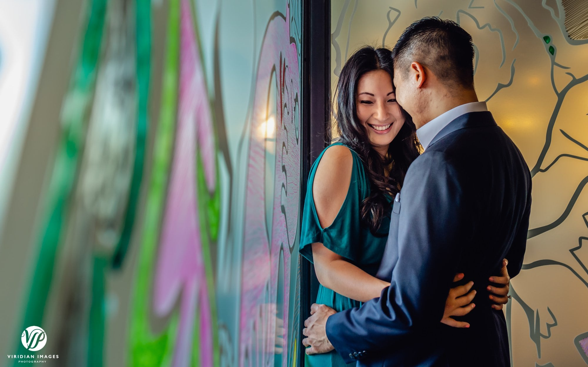 bashful couple in corner hugging