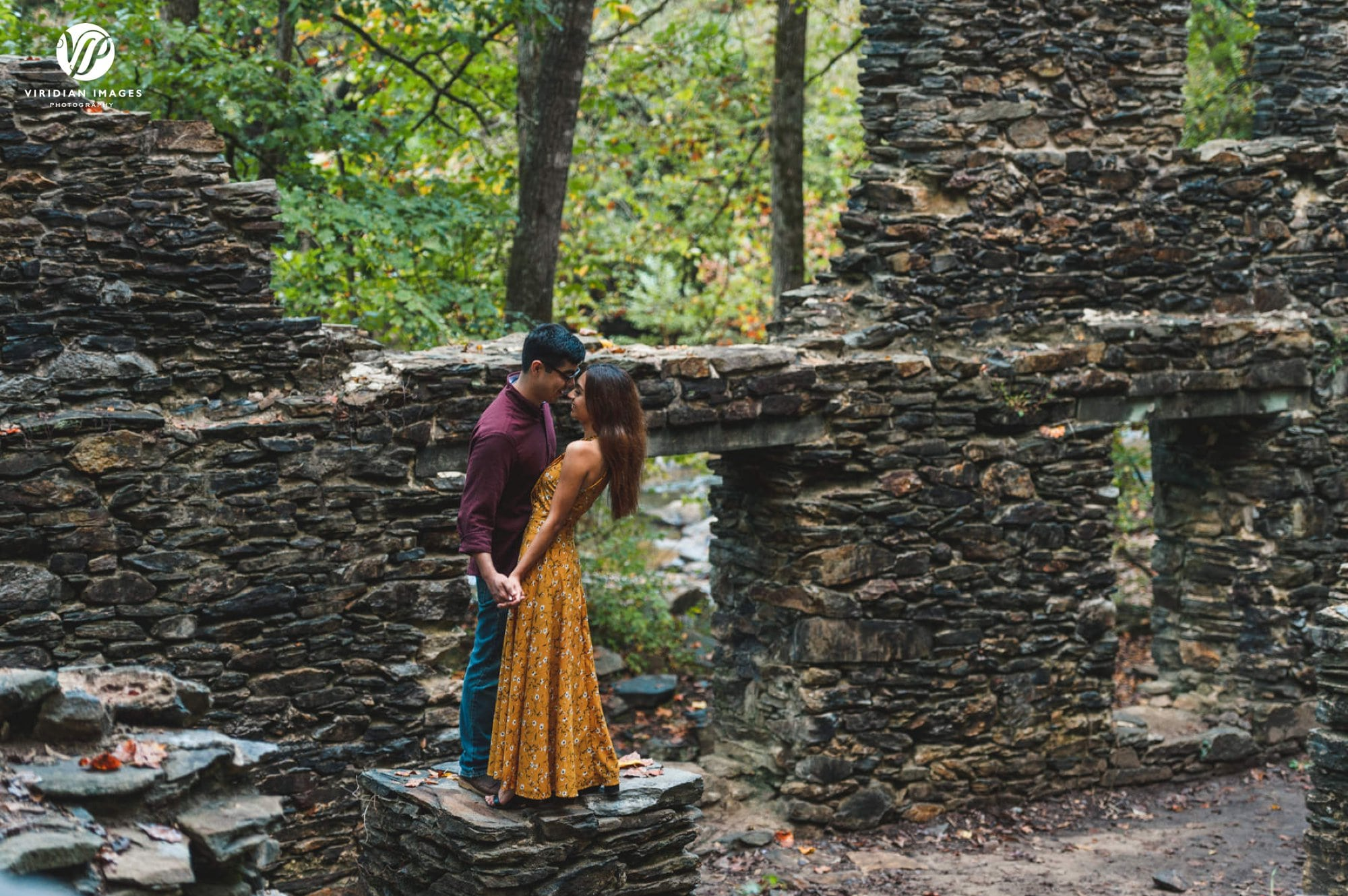 Couple embrace in old mill ruins