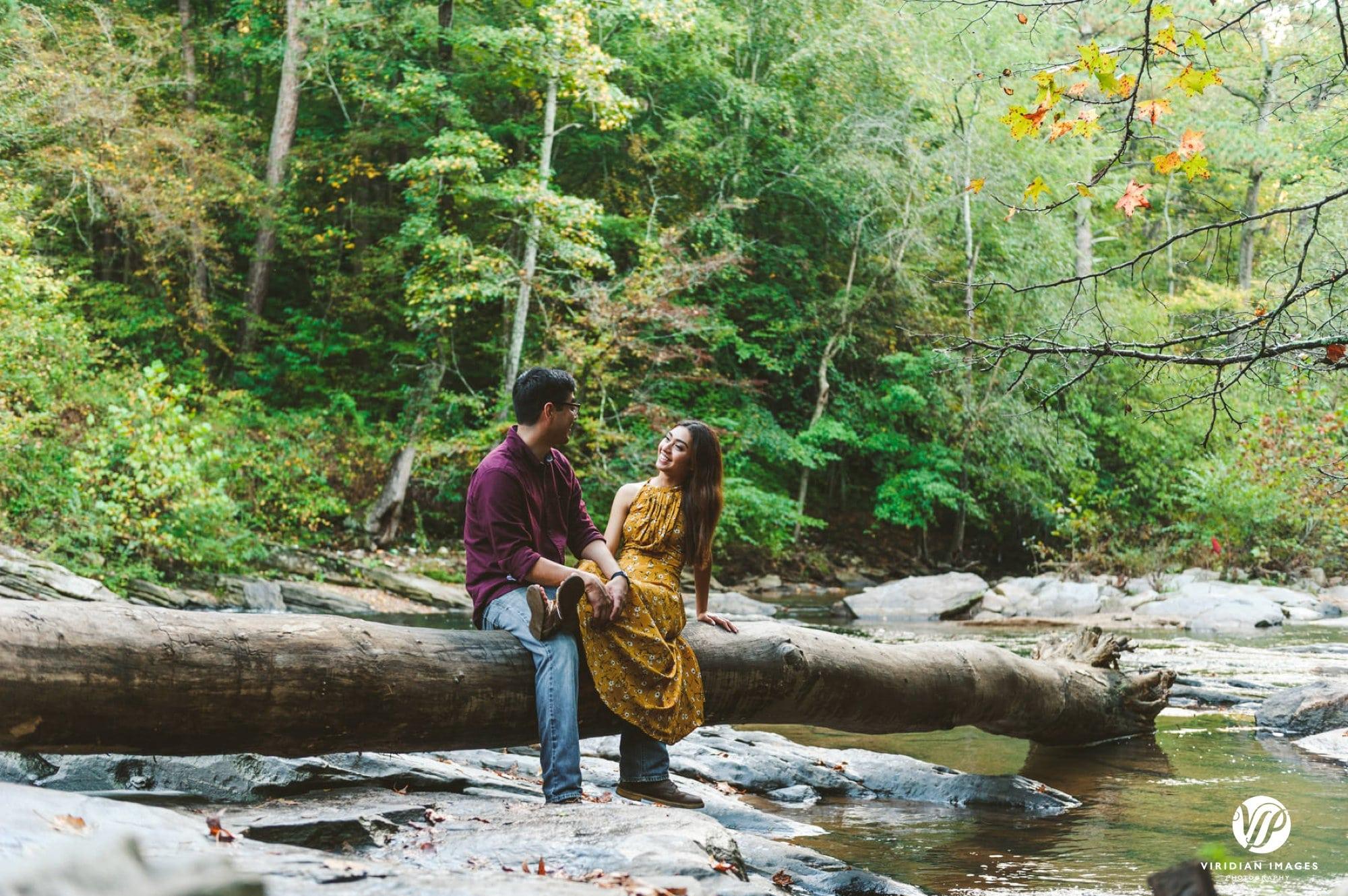 couple talking on fallen tree along river