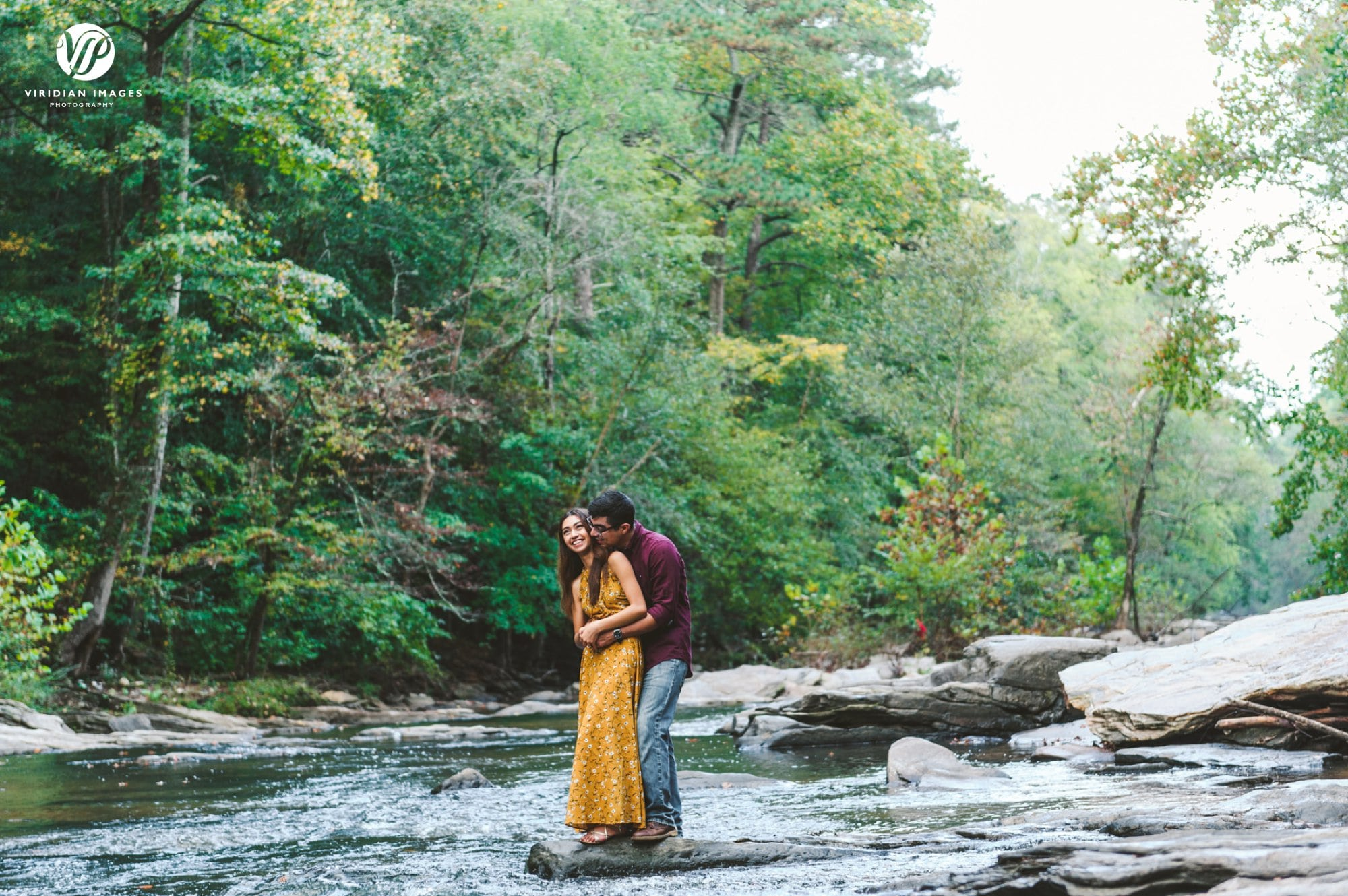 couple hugging on rock middle of chattahoochee river