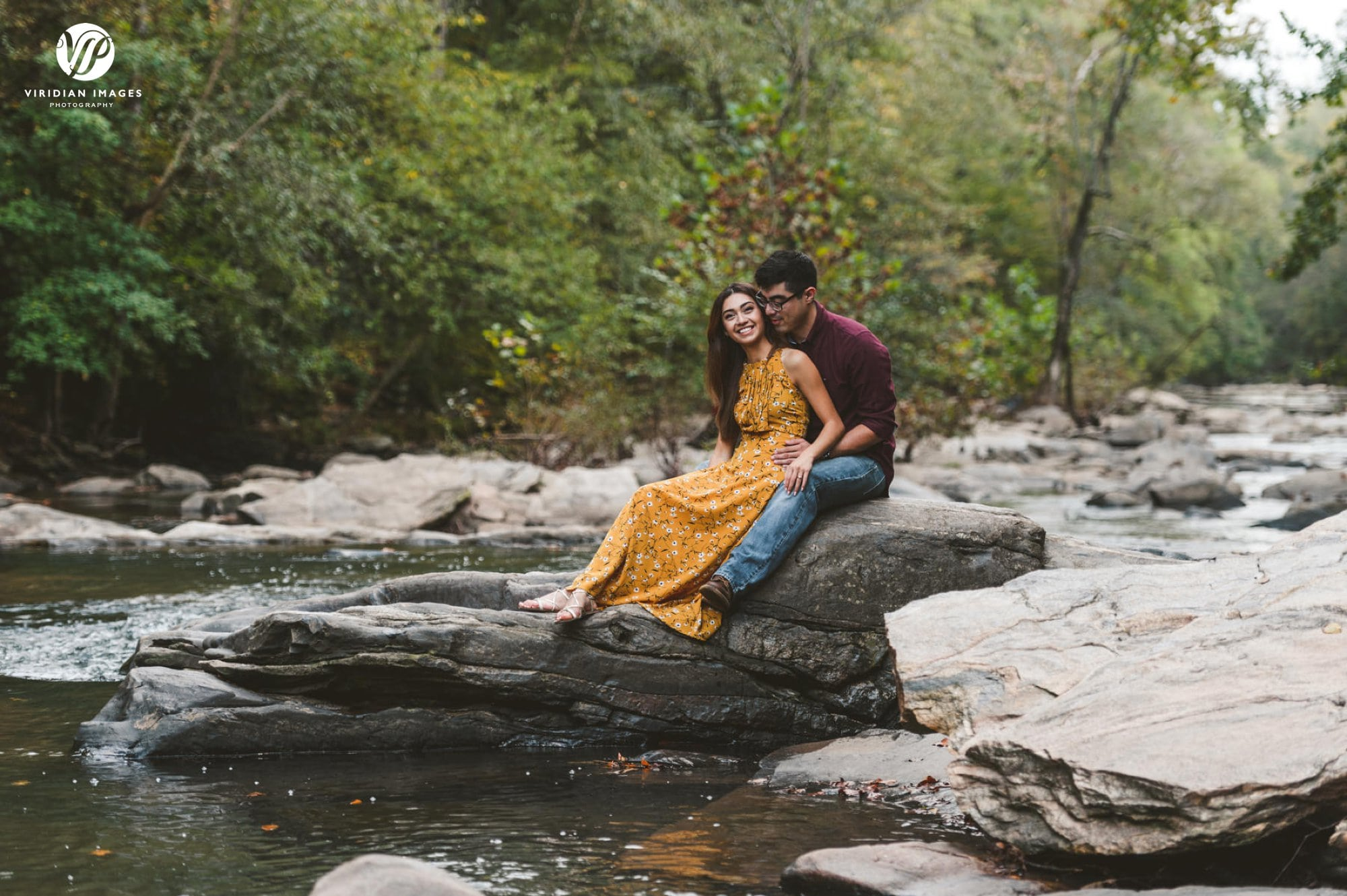 couple sitting on rock of chattahoochee river
