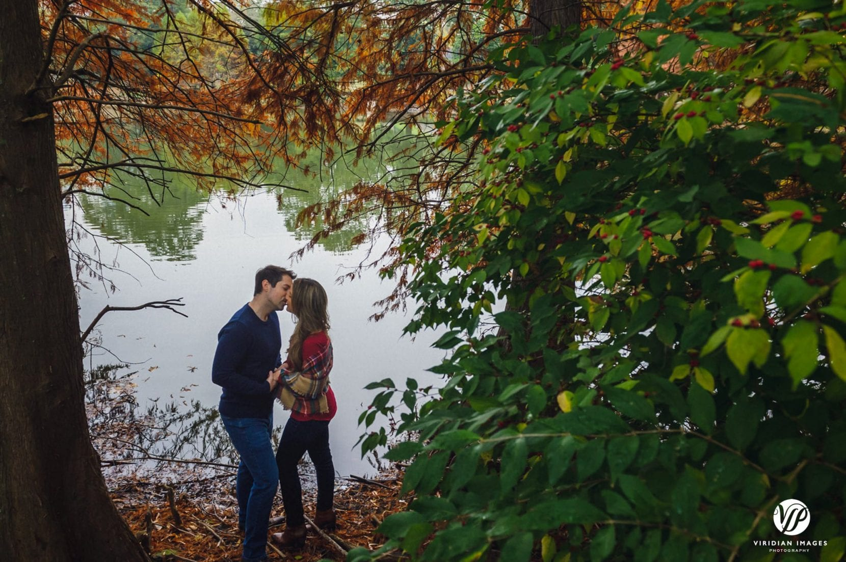 couple kissing by lake at piedmont park engagement photo