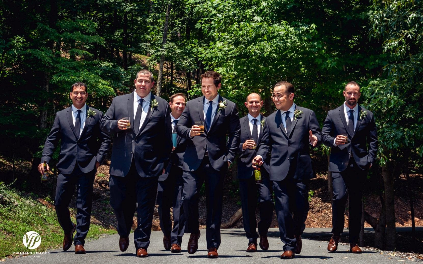 groomsmen having drinks while walking to wedding