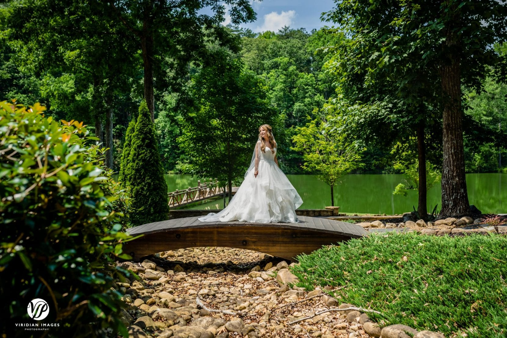 bride portrait on dry creek bridge near lake and dock