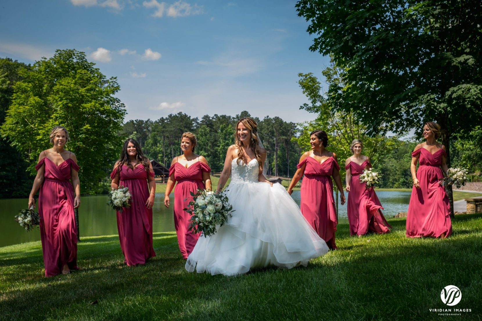 bride and bridesmaids walking on lawn near lake