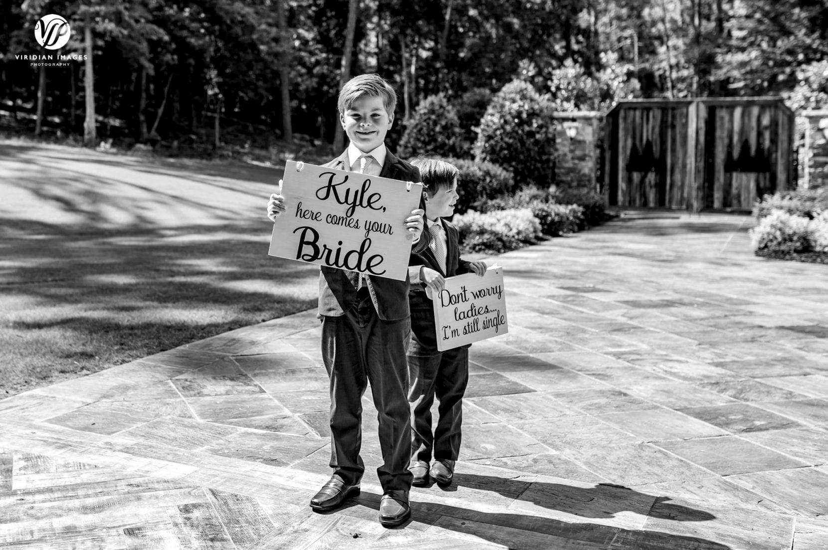 cute ring bearers ready with cute signs for groom about bride