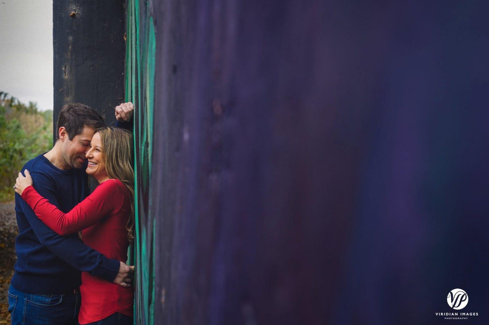 couple embrace and laugh near mural at piedmont park