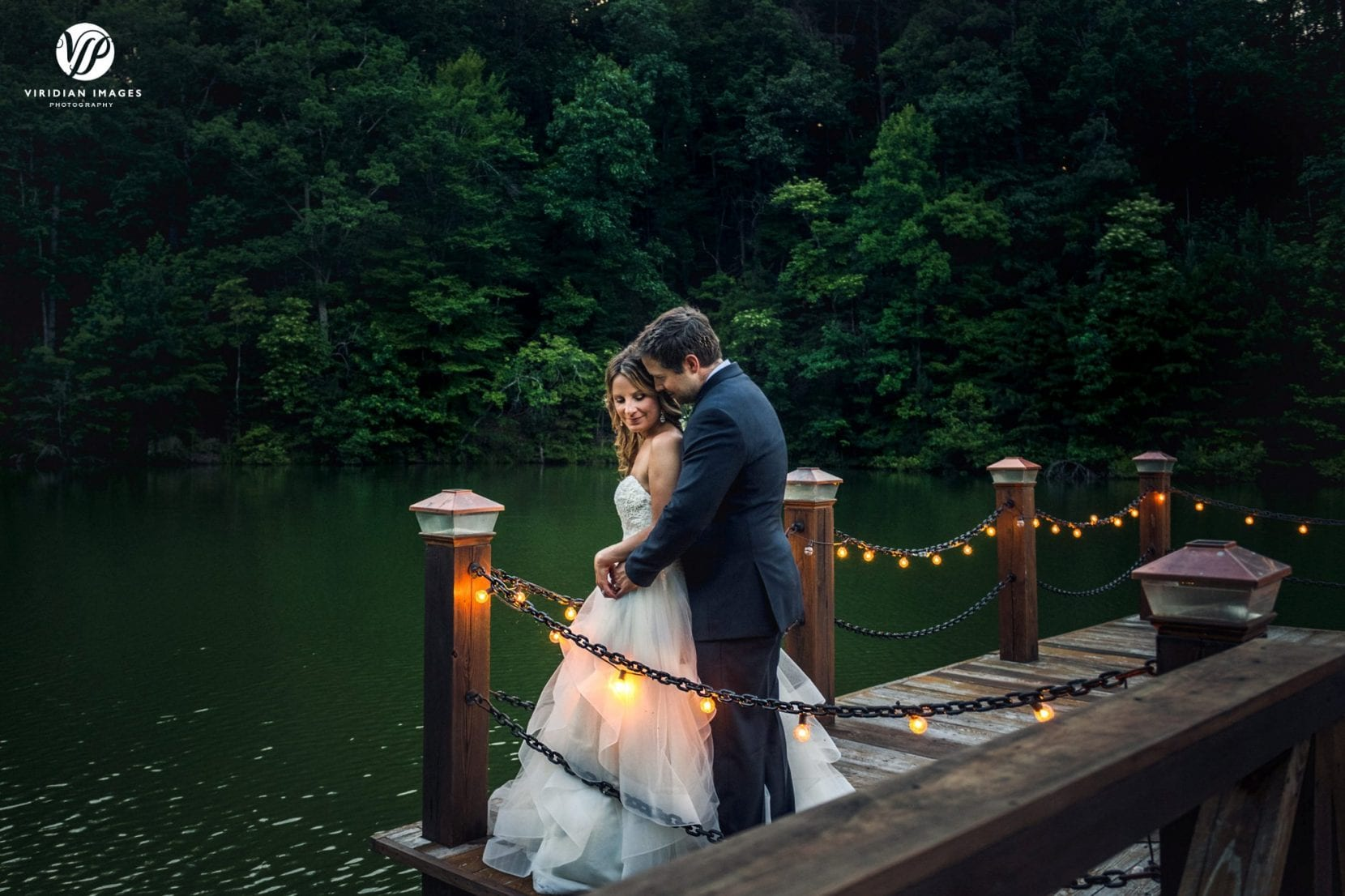 romantic portrait of bride and groom on dock at dusk