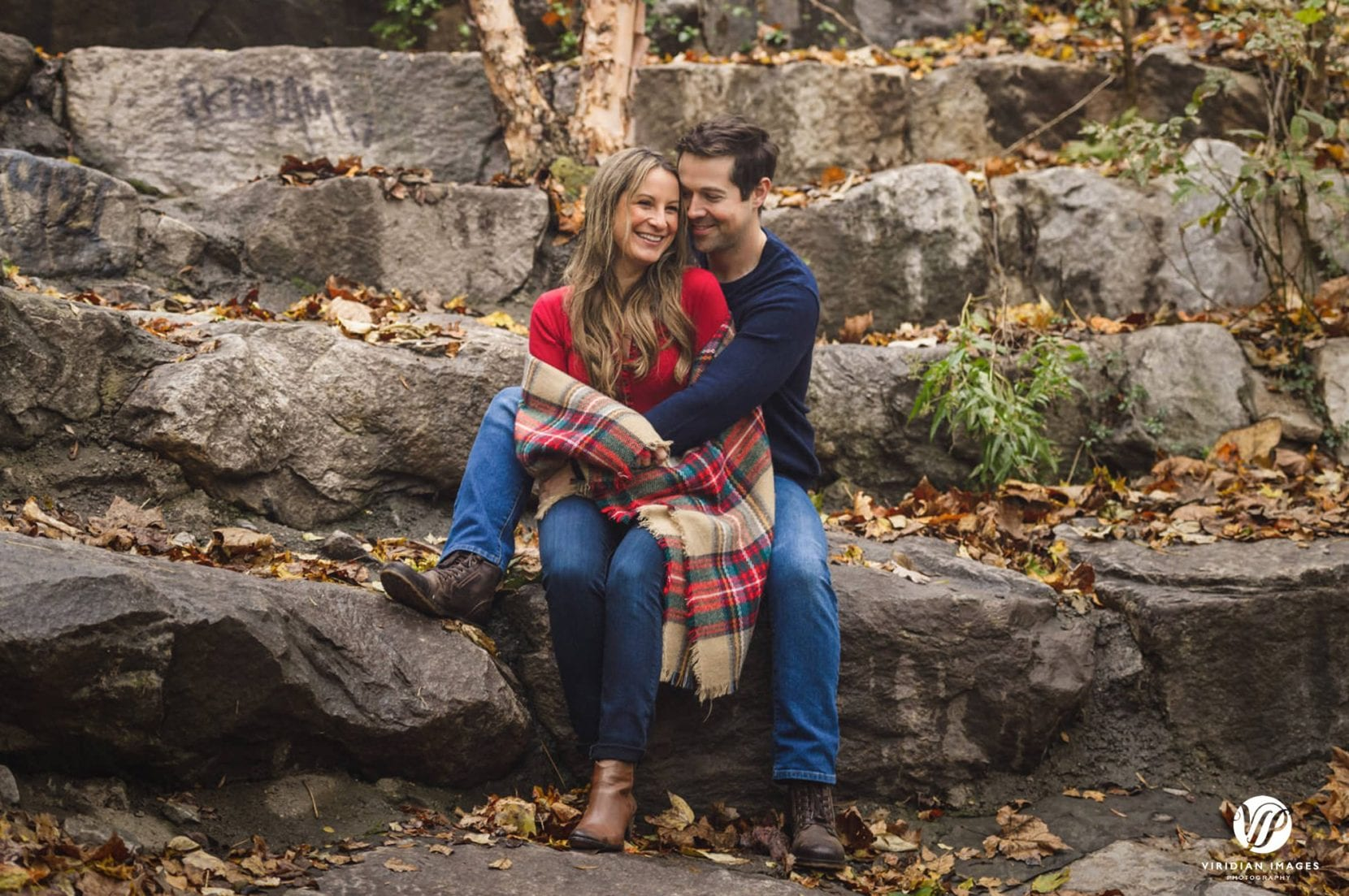 couple sit and embrace on rocks at piedmont park engagement photo