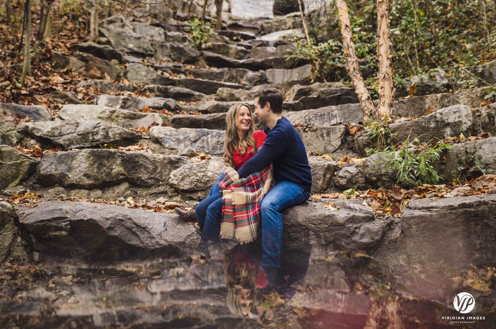 couple sit on rocks at piedmont park engagement photos