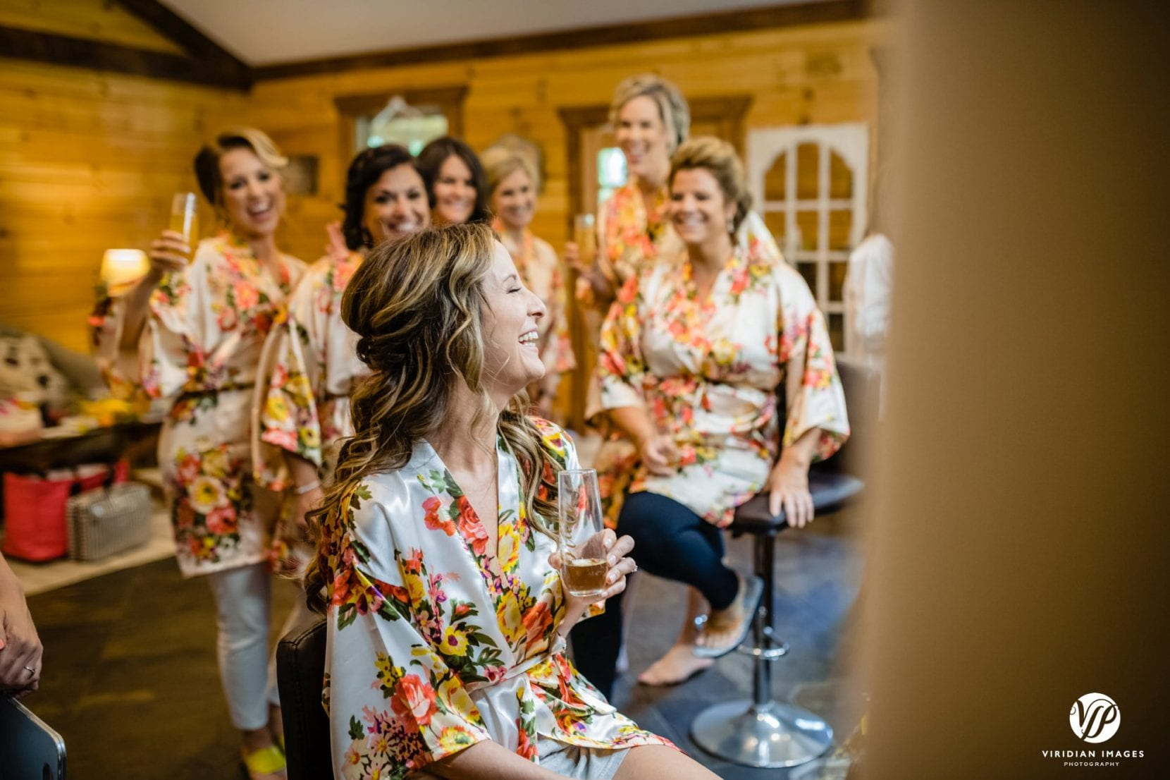 bride drinking champagne with bridesmaids in floral robes laughing