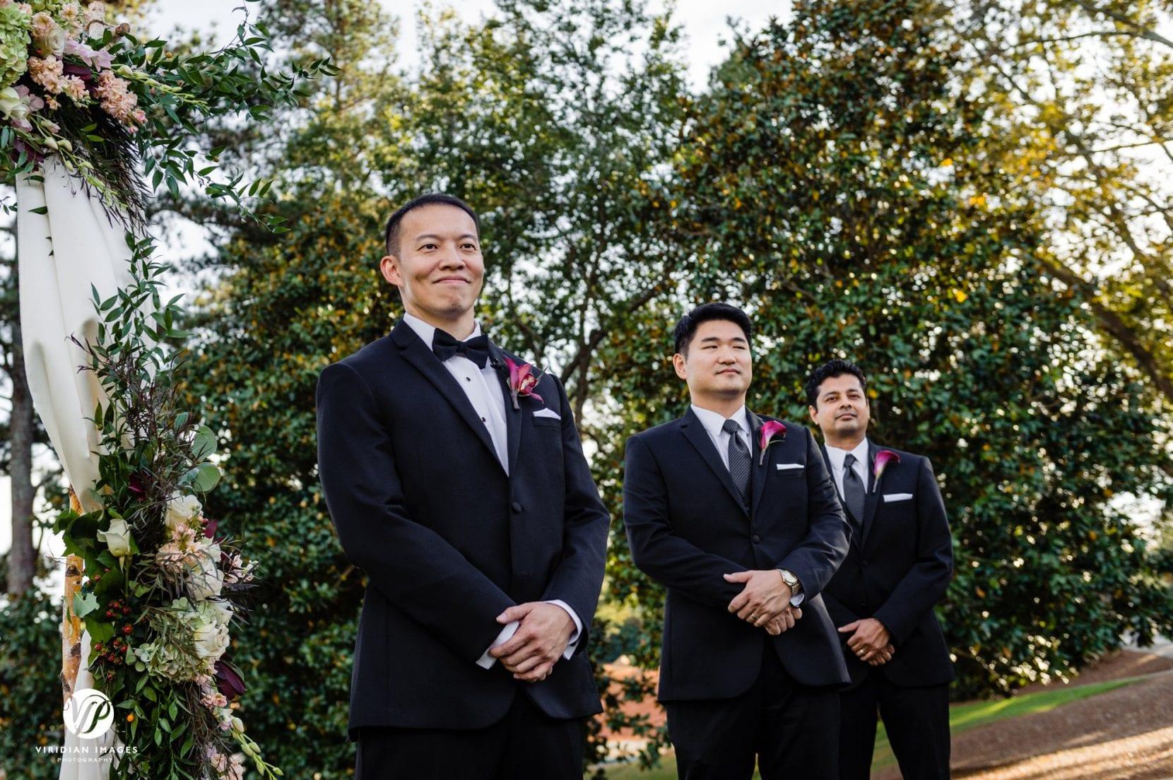groom watching bride down aisle