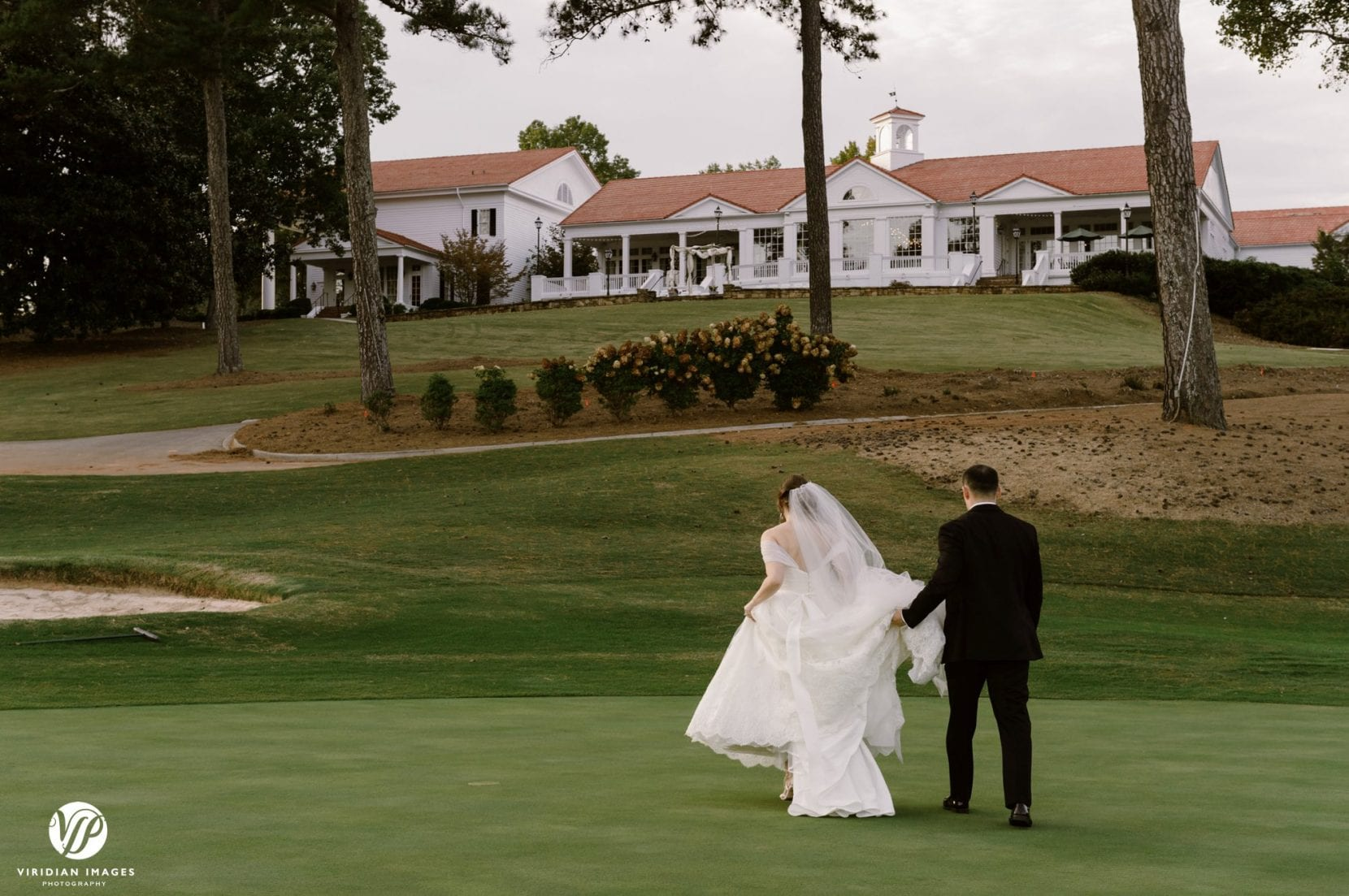 bride and groom walking towards clubhouse