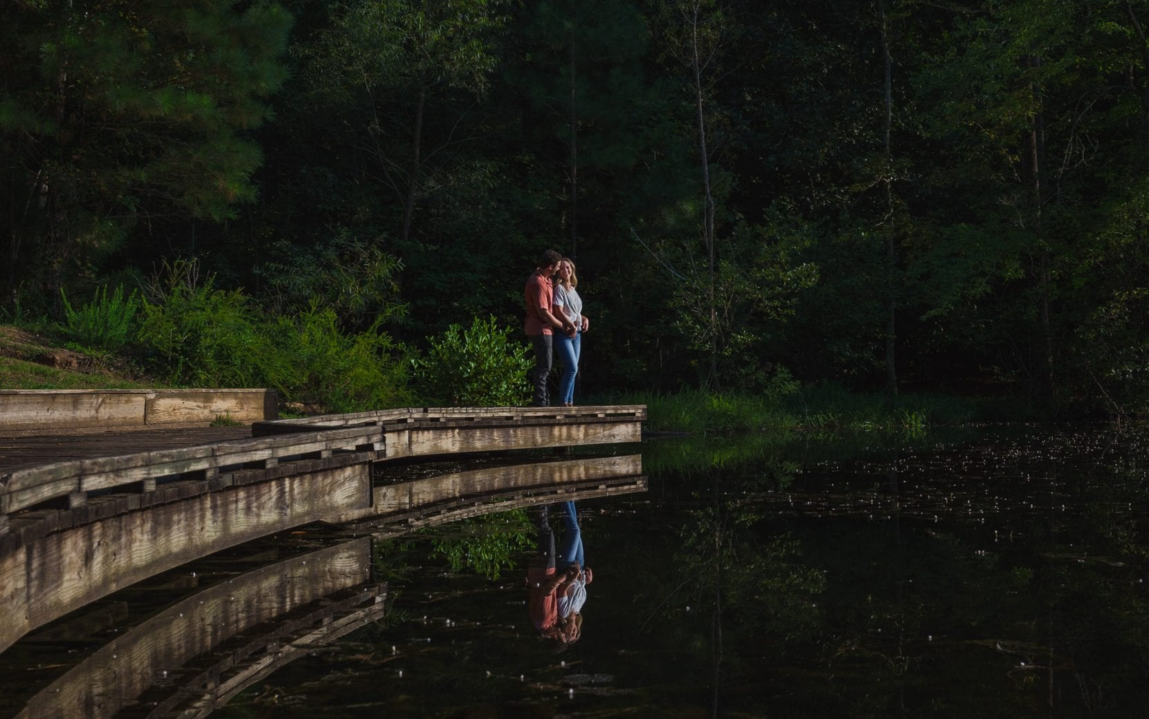 couple on dock engagement hugging