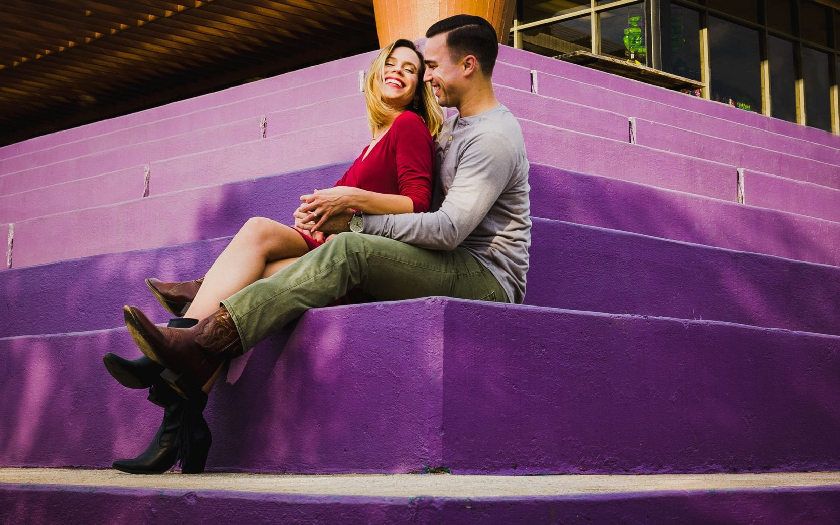 happy couple sitting purple stairs engagement