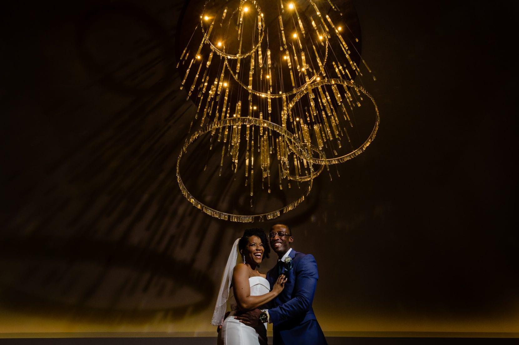 wedding couple under chandelier
