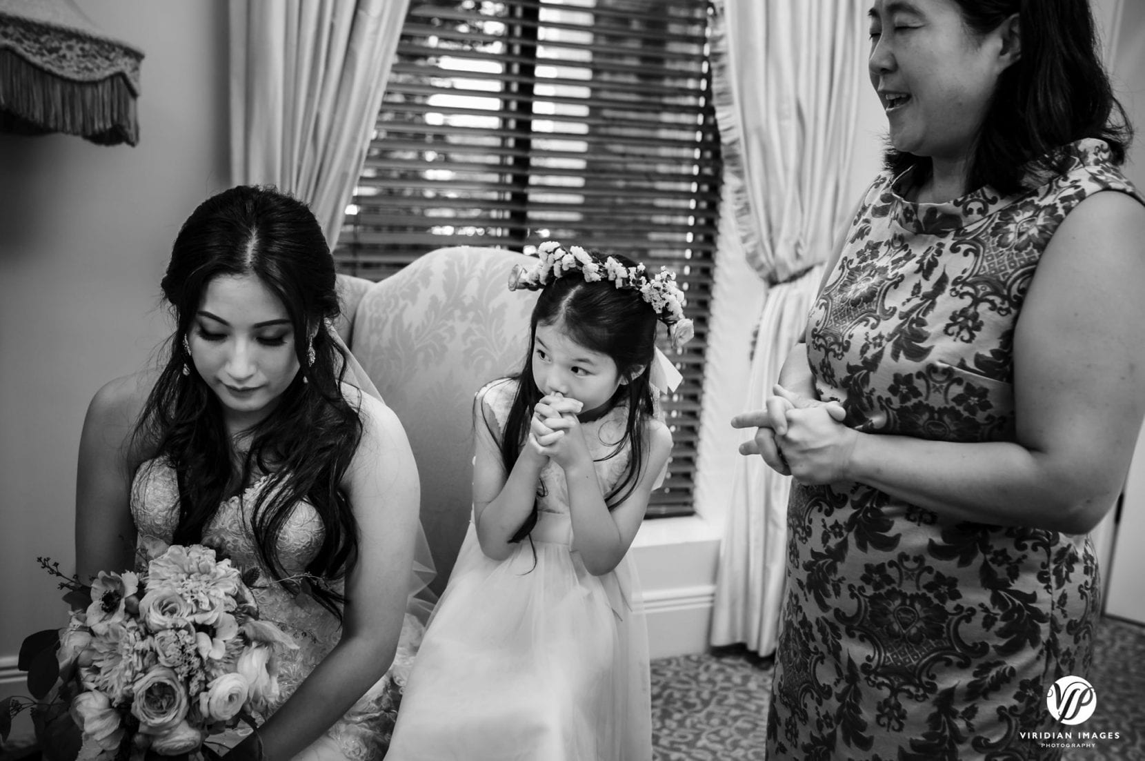 bride and flower girl with paster praying