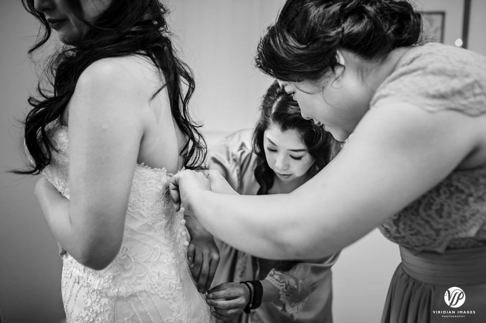 bridesmaids helping bride wedding dress