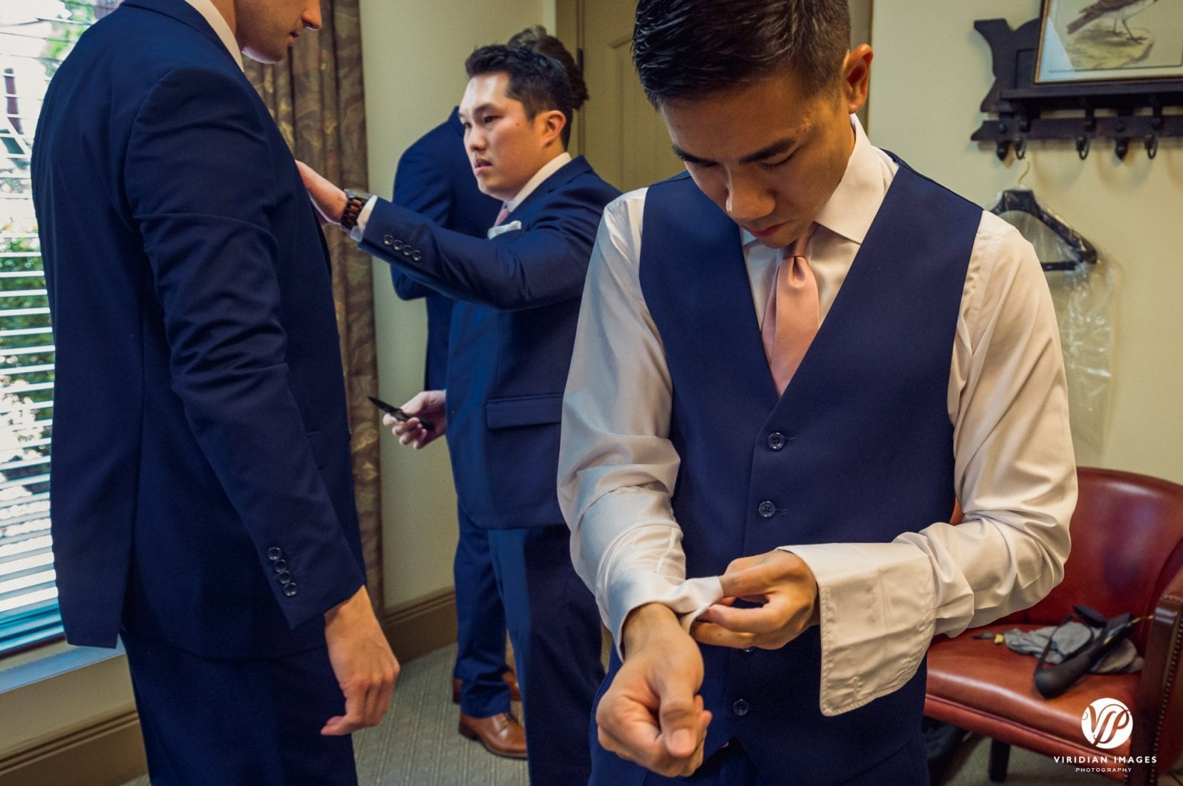 groom putting on cufflinks getting ready