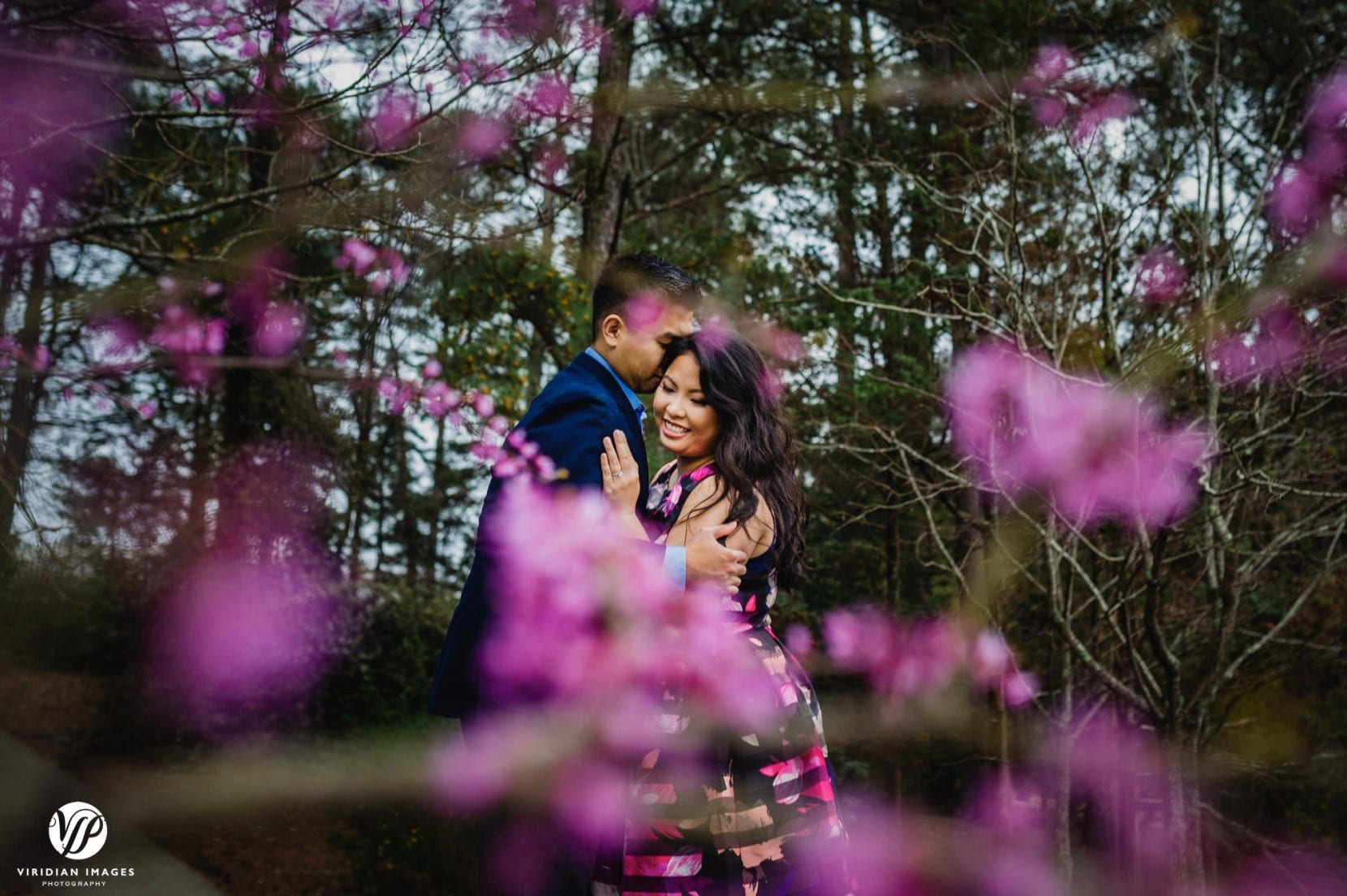 couple hugging through flowering trees in stone mountain park engagement photo
