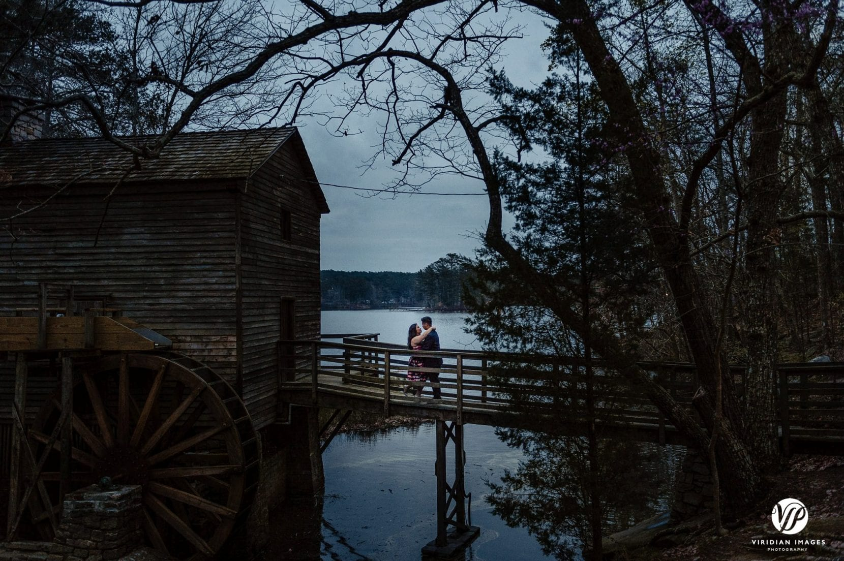 couple hugging water wheel lake in atlanta stone mountain park engagement photo