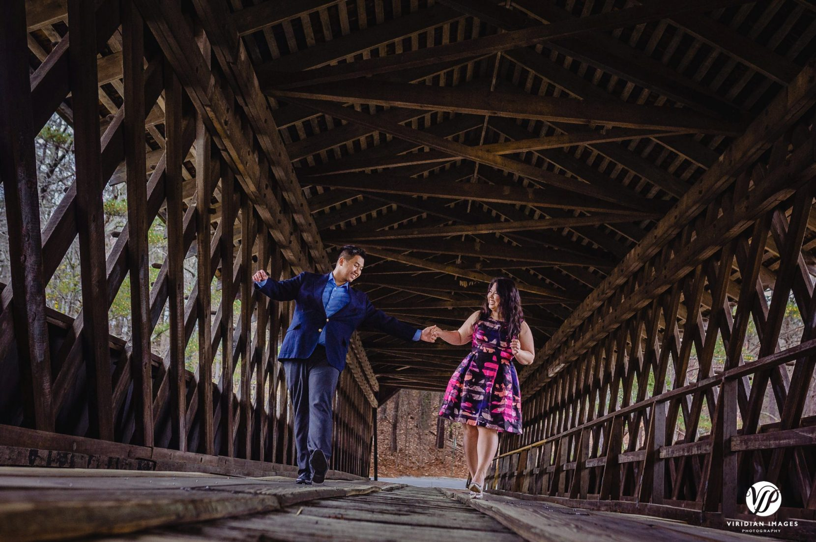 couple playful keeping balance covered bridge in atlanta stone mountain park engagement photo