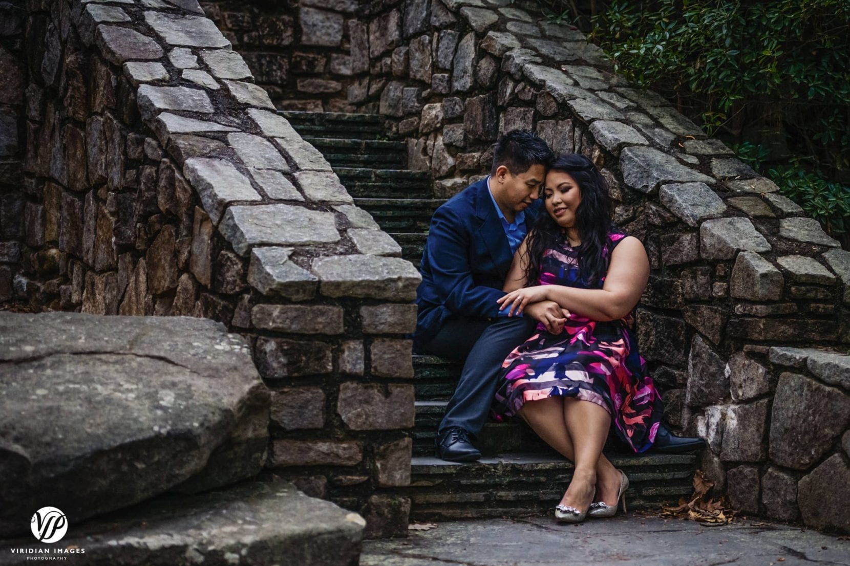 couple sitting on stone stairs dusk in stone mountain park atlanta engagement photo