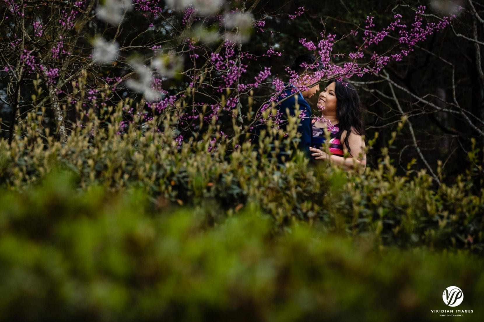couple smiling flowering trees in stone mountain park atlanta engagement photo