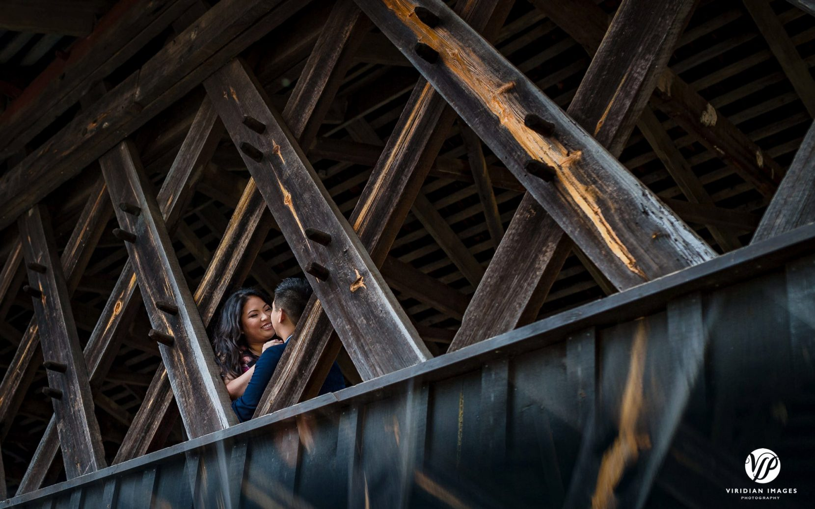 romantic couple face to face covered bridge in atlanta stone mountain park engagement photo