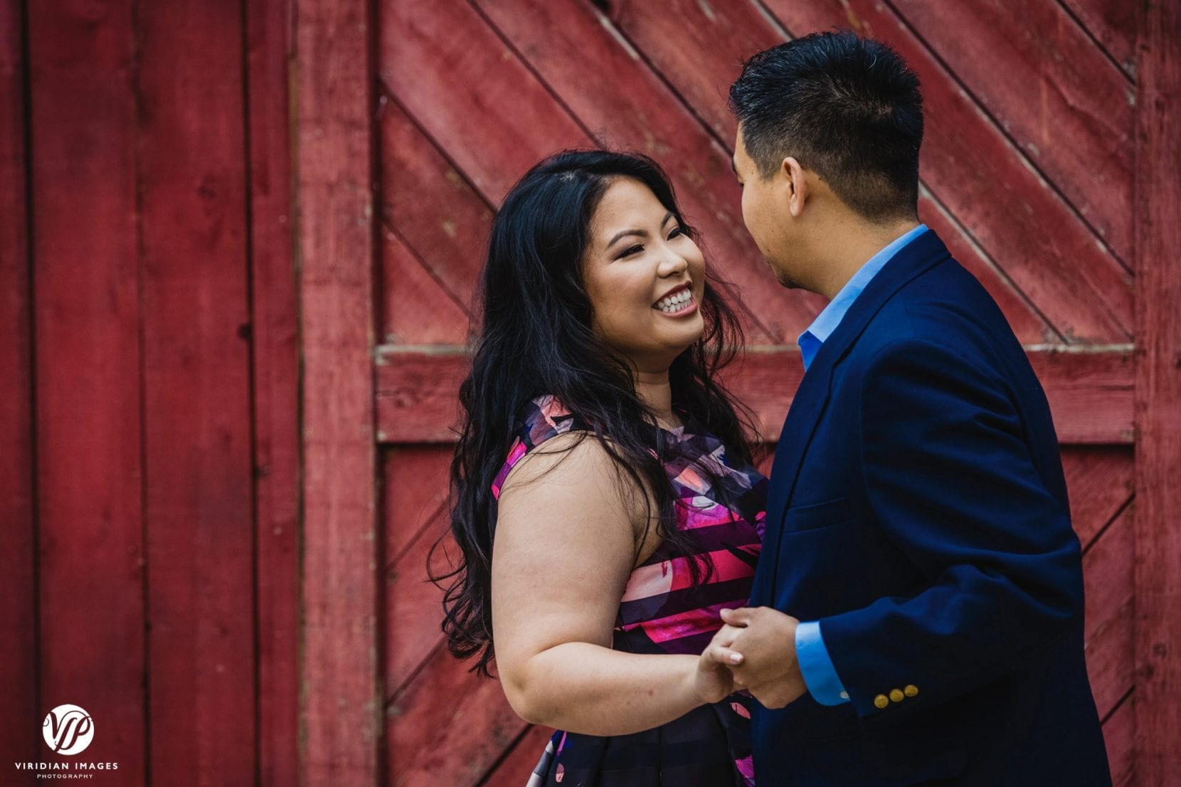 bride smiling at groom red barn door in stone mountain park engagement photo atlanta