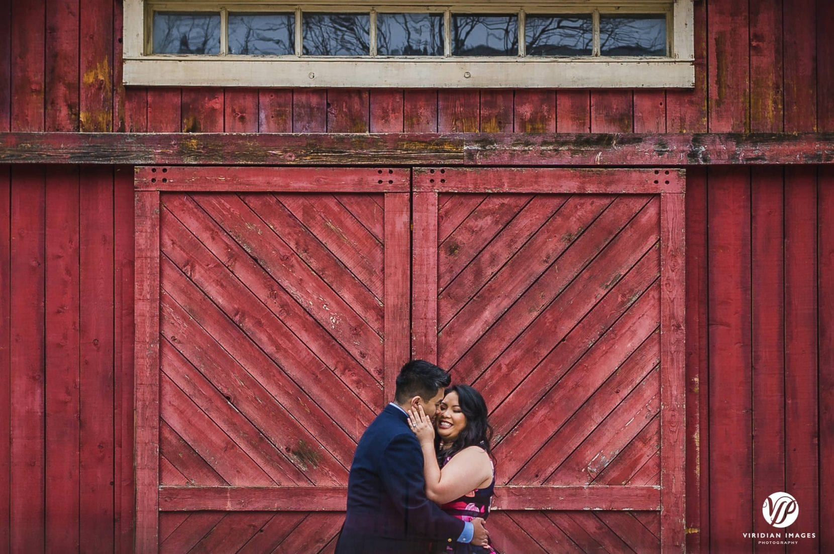 couple romantic hugging front of red barn door in stone mountain park engagement photo