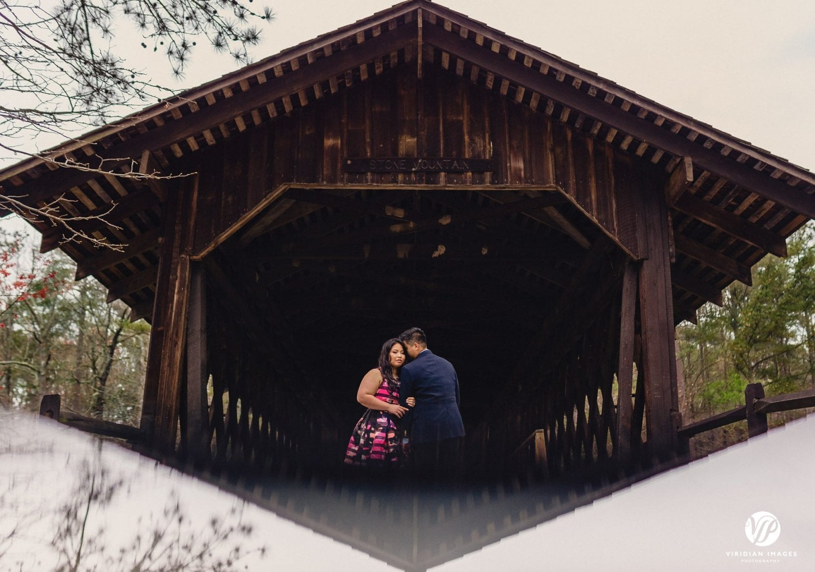 couple reflection covered bridge in stone mountain park atlanta engagement photo